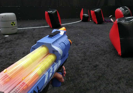 a kid shooting balls using yellow nerf war gun